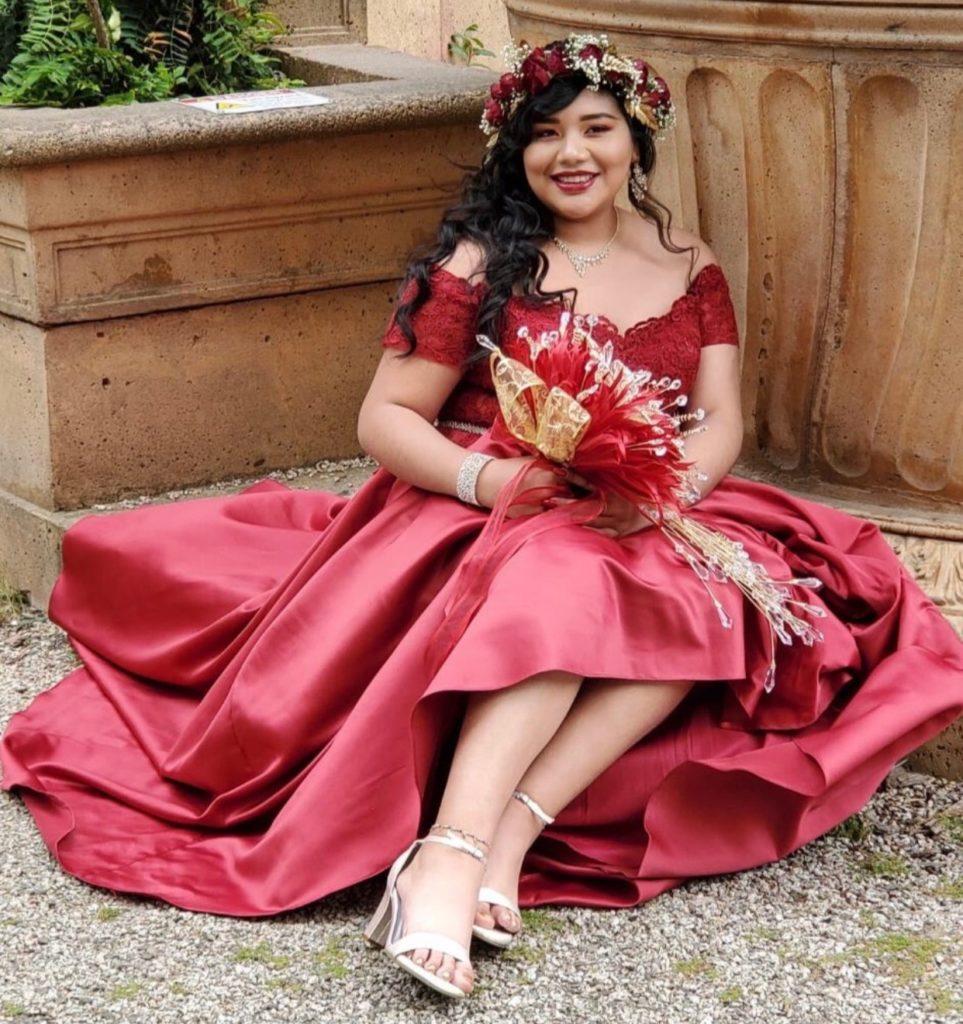 Brandy sentado afuera en un escalón con un vestido rojo, flores y corona de flores.